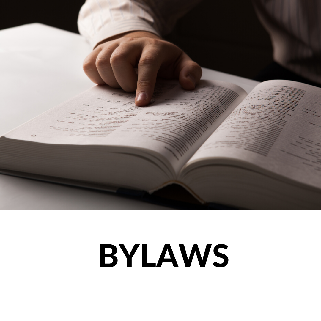 finger searching through a thick book, the word bylaws under the photo